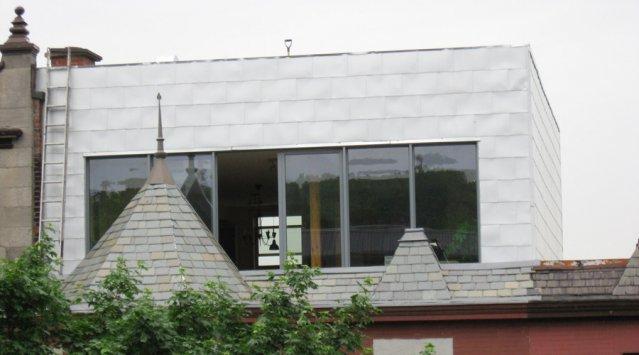 Une maison ancienne additionnée d'un étage avec toit vert. Photo Écohabitation.